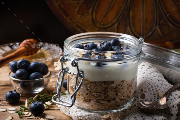 Muesli with yogurt and blue berries in glass jar. - Stock Photo - Images