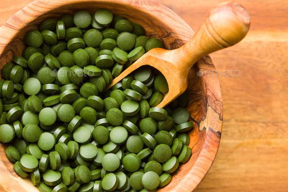 Green chlorella pills or green barley pills in bowl. - Stock Photo - Images