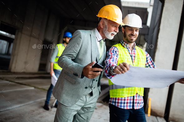 Confident team of architects and engineers working together on construction site - Stock Photo - Images
