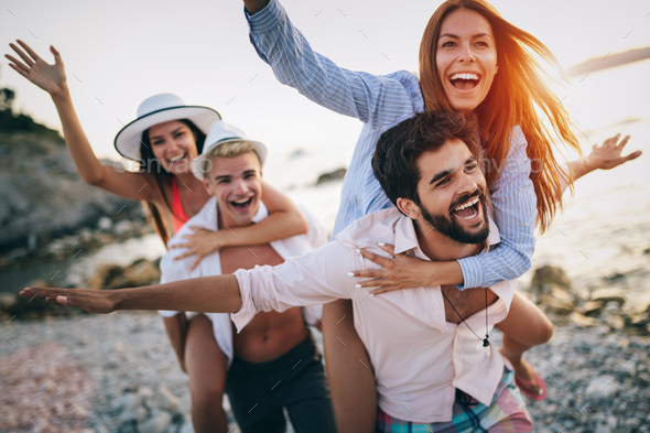 Cheerful friends enjoying weekend and having fun on beach Stock Photo by nd3000