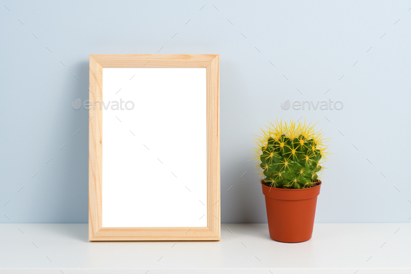 Cactus in pot and wooden photo frame on shelf - Stock Photo - Images
