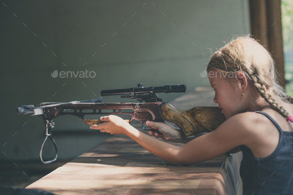 girl shoots a rifle in the dash - Stock Photo - Images