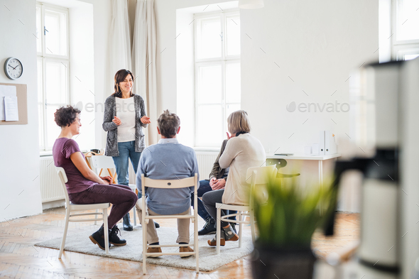 A woman talking to other people during group therapy. - Stock Photo - Images