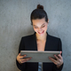 Young business woman with tablet standing against concrete wall in office. - PhotoDune Item for Sale