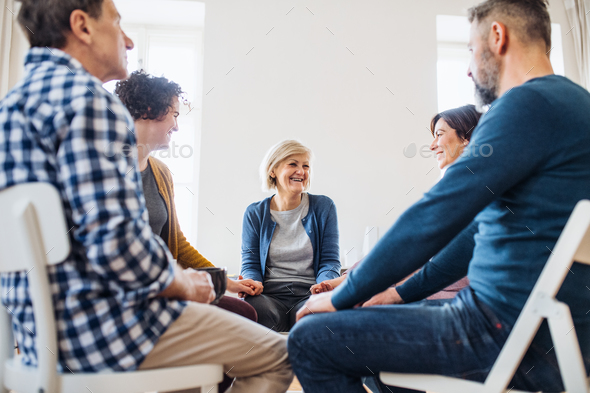 Men and women sitting in a circle and holding hands during group therapy. - Stock Photo - Images