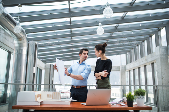 Two young architects with blueprints and model of a house standing in office, talking. - Stock Photo - Images