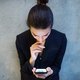 A top view of young business woman with smartphone standing against concrete wall in office. - PhotoDune Item for Sale