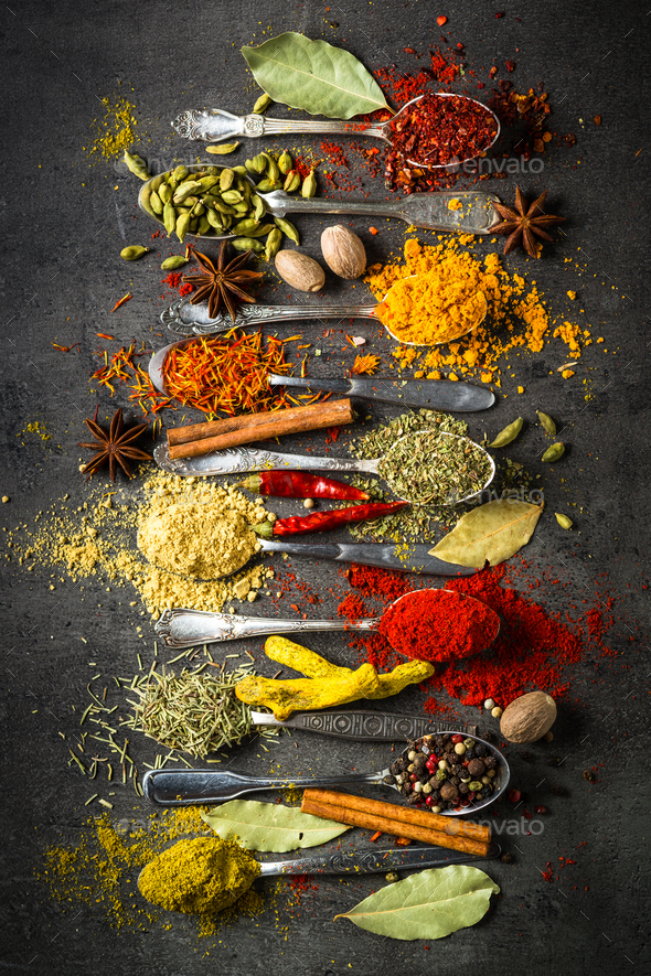Spices in spoons on black background. - Stock Photo - Images