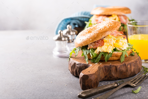 Bagels with scrambled eggs, rucola and fried bacon - Stock Photo - Images