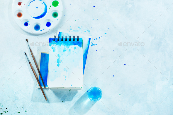 Painting spring concept with artist tools, green and blue watercolor  sketchbooks, brushes and color