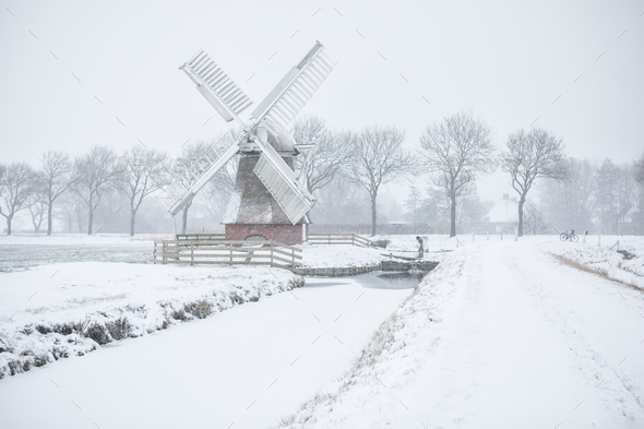 Dutch windmill in snowfall during winter - Stock Photo - Images
