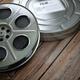 Vintage film reel with filmstrip on wood background. Video, cine - PhotoDune Item for Sale