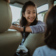 portrait of young woman driver looking back at a little girl - PhotoDune Item for Sale
