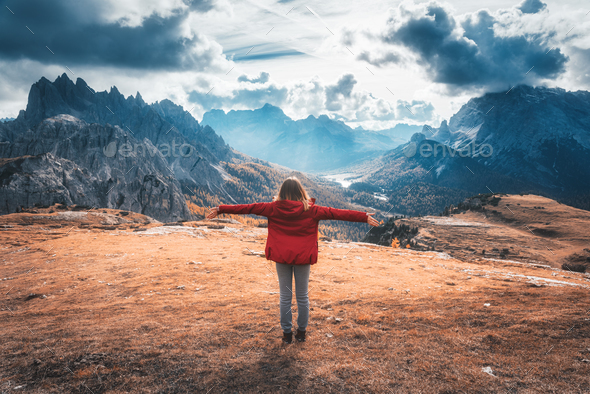 Young woman with raised up arms and mountains at sunset - Stock Photo - Images