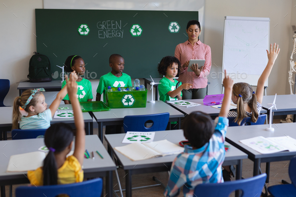 Schoolkids studying about green energy at desk in classroom - Stock Photo - Images