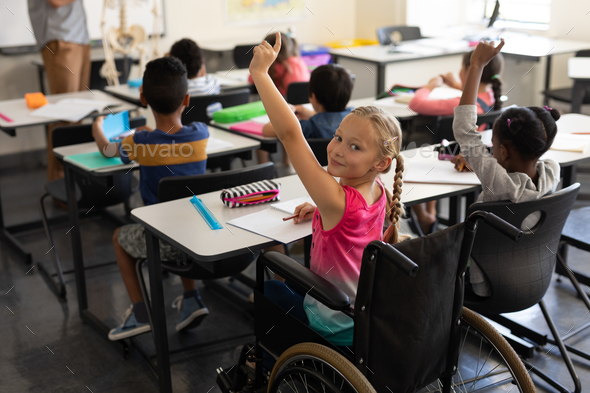 Smiling disable schoolgirl looking at camera and raising hand in classroom of elementary school - Stock Photo - Images