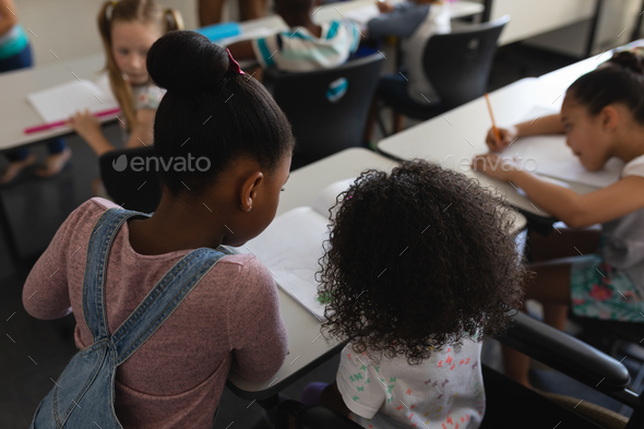 Rear view of schoolgirls studying together at desk in classroom of elementary school - Stock Photo - Images