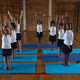 Front view of schoolkids doing yoga on a yoga mat in school - PhotoDune Item for Sale