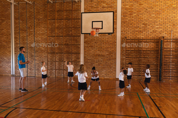 Basketball coach teaching to schoolkids at basketball court in school - Stock Photo - Images