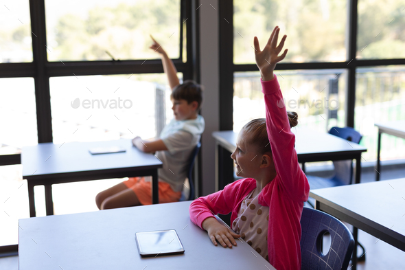 Side view of school kids raising their  hand while sitting at desk in classroom of elementary school - Stock Photo - Images