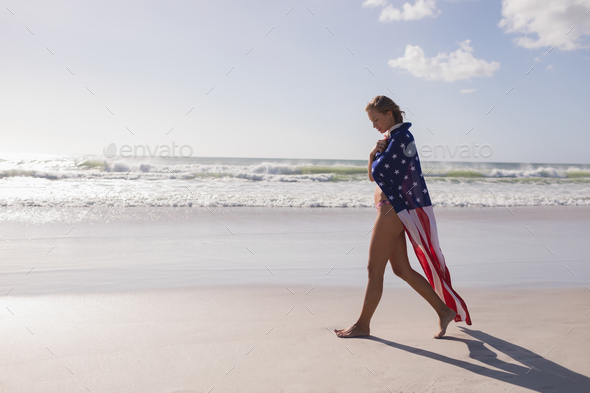 Side view of young woman wrapped in American flag at beach on a sunny day - Stock Photo - Images