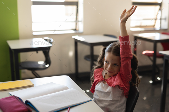 Side view of a smiling schoolgirl raising hand in classroom while sitting at desk - Stock Photo - Images