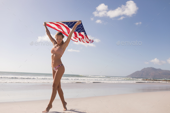 Young woman holding waving American flag at beach on a sunny day - Stock Photo - Images