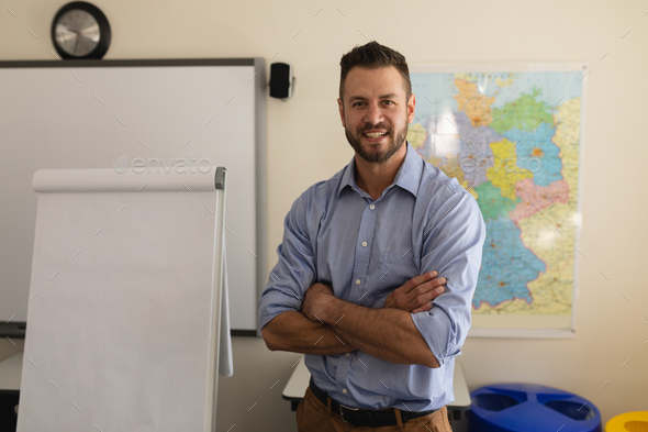 Happy school teacher with arms folded looking at camera and standing in a classroom - Stock Photo - Images