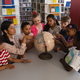 Front view of female teacher teaching the kids about the globe at table in school library - PhotoDune Item for Sale