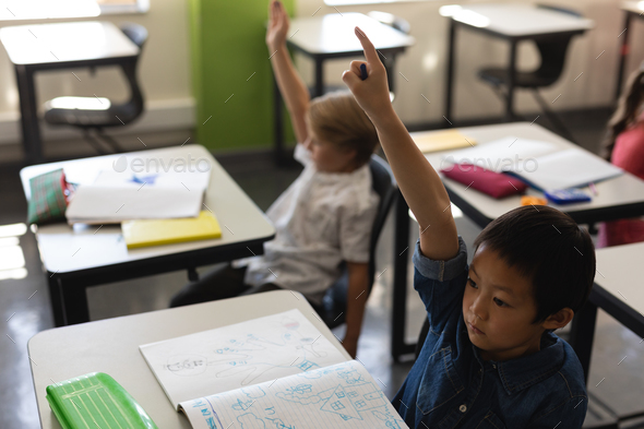 High angle view of schoolboy raising hand in classroom while sitting at desk - Stock Photo - Images