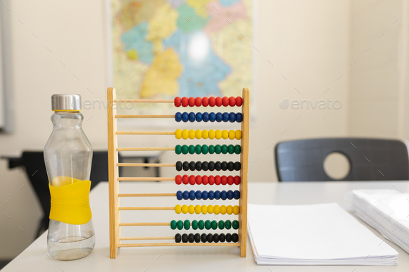 Close-up of water bottle, abacus and bunch of paper on the desk in school - Stock Photo - Images