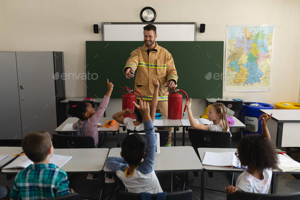 Schoolkids raising hands while firefighter teaching about fire safety of elementary school   - Stock Photo - Images