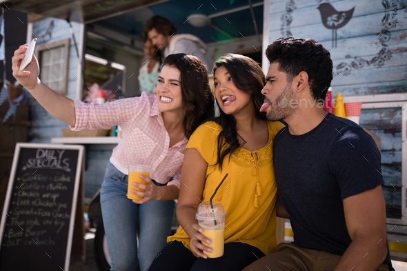 Happy friends taking selfie from mobile phone in food truck van - Stock Photo - Images