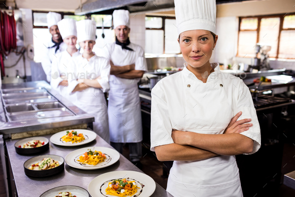Female chef standing with arms crossed in kitchen at hotel - Stock Photo - Images