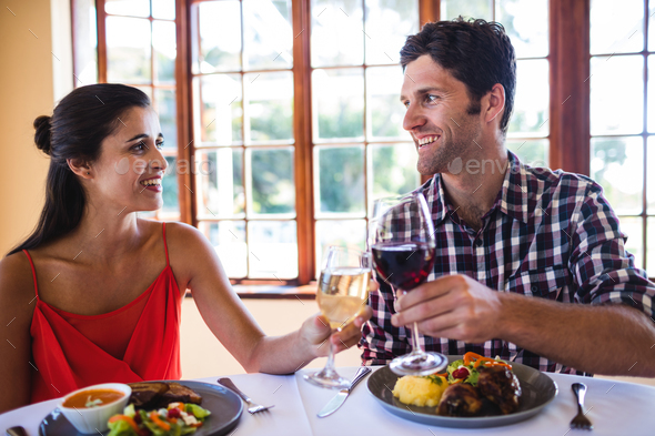 Smiling couple toasting wine glass at the table in restaurant - Stock Photo - Images