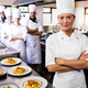 Female chef standing with arms crossed in kitchen at hotel - PhotoDune Item for Sale