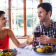 Smiling couple toasting wine glass at the table in restaurant