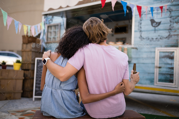 Rear view of romantic couple sitting with beer bottle near food truck - Stock Photo - Images