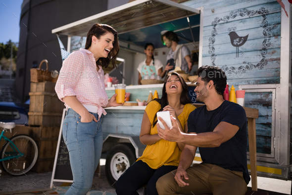Friends looking at mobile phone and smiling in food truck van - Stock Photo - Images