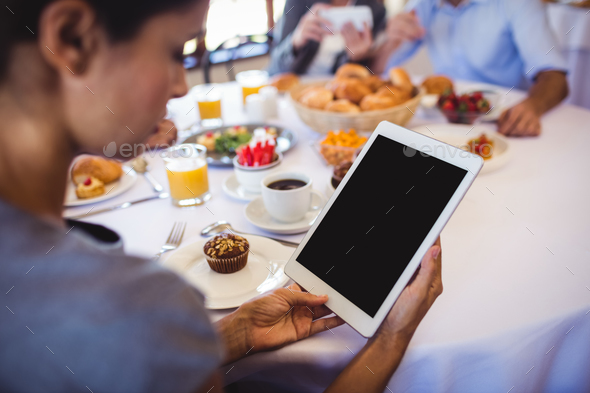 Close-up of businesswoman using digital tablet in restaurant - Stock Photo - Images
