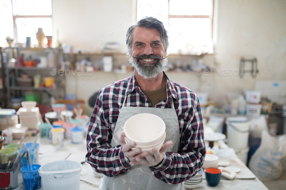 Proud male potter showing his creation to camera in the pottery workshop - Stock Photo - Images