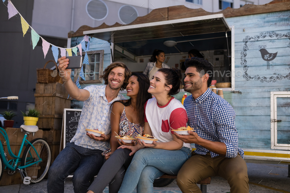 Smiling friends taking selfie from mobile phone - Stock Photo - Images
