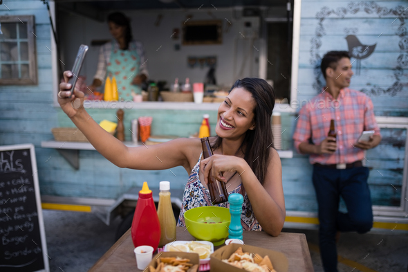 Beautiful woman taking selfie from mobile phone in cafeteria - Stock Photo - Images