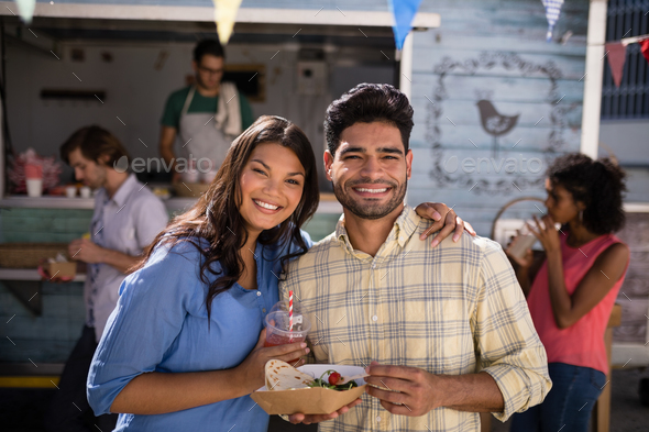 Portrait of smiling couple standing with snacks and juice - Stock Photo - Images