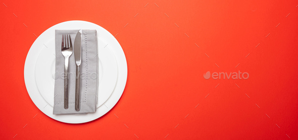 Set of empty white plates and cutlery on red, orange color background, banner - Stock Photo - Images