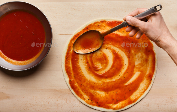 Chef hand spreading tomato paste on pizza base - Stock Photo - Images