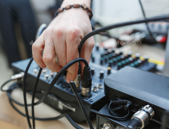 DJ connects the sound equipment for the event or party. - Stock Photo - Images