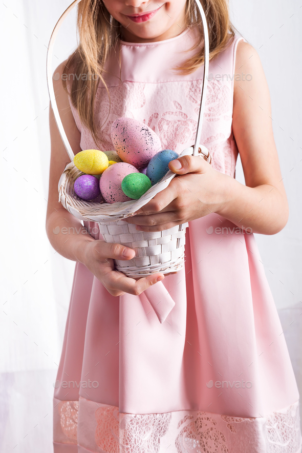 Cute little child holding basket with painted eggs on Easter day. - Stock Photo - Images