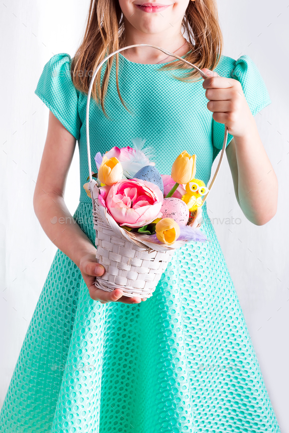 Cute little child holding basket with painted eggs and flowers on Easter day. - Stock Photo - Images