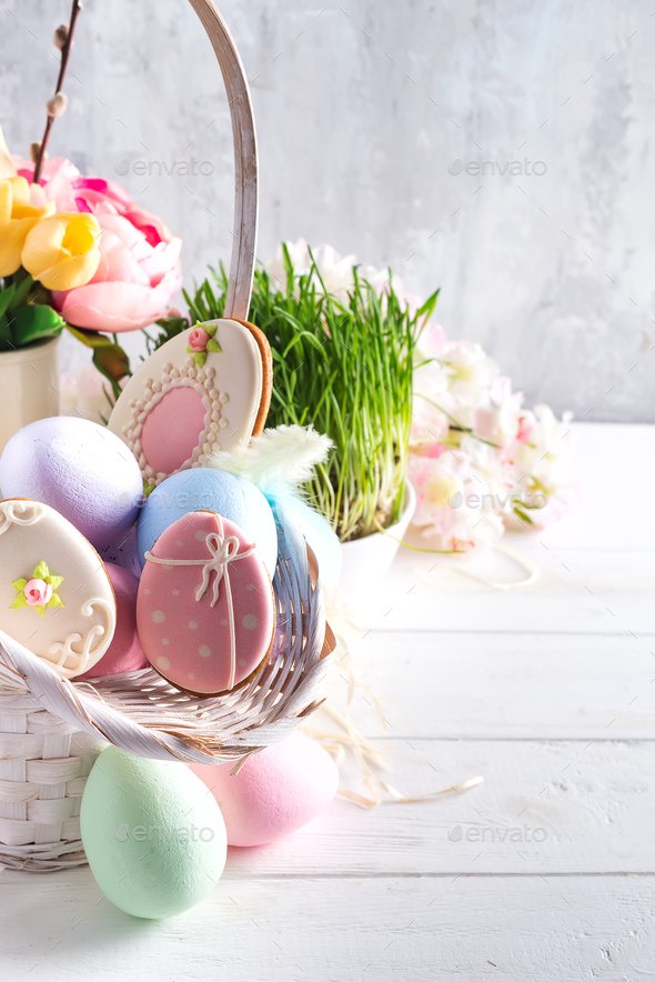 Easter greeting card with glazed cookies and colorful easter eggs in basket . With copy space - Stock Photo - Images